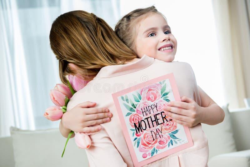 Filha com o cartão à disposição que abraça a mãe no dia do ` s da mãe fotos de stock royalty free