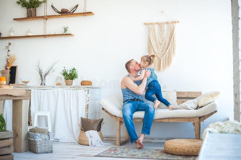 A filha com o pai na sala da cozinha está jogando Relacionamento na família Menina que joga com paizinho foto de stock