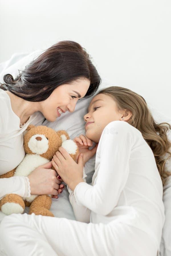 Filha com o urso e a mãe de peluche que relaxam na cama em casa fotos de stock