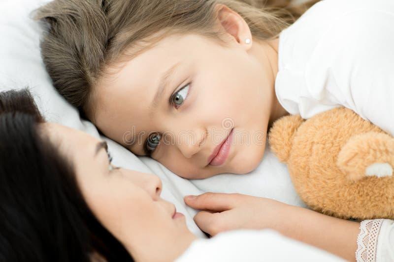 Filha com o urso e a mãe de peluche que relaxam na cama em casa imagens de stock royalty free