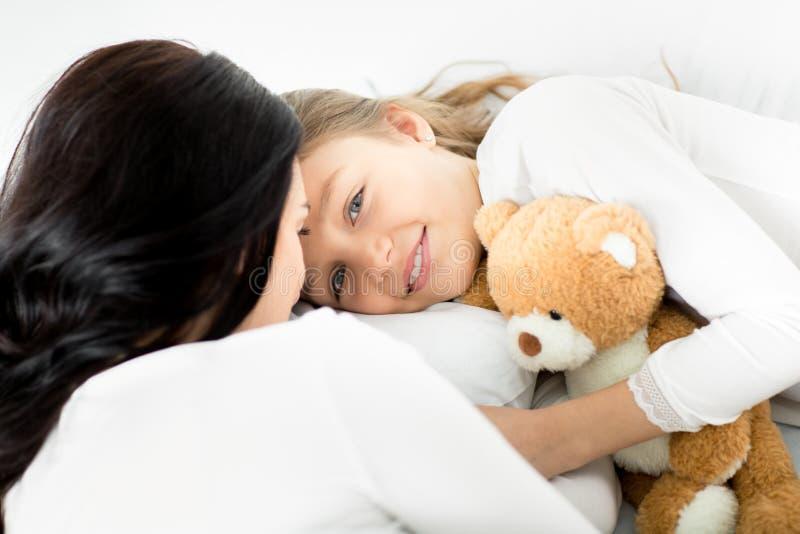 Filha com o urso e a mãe de peluche que relaxam na cama em casa imagens de stock