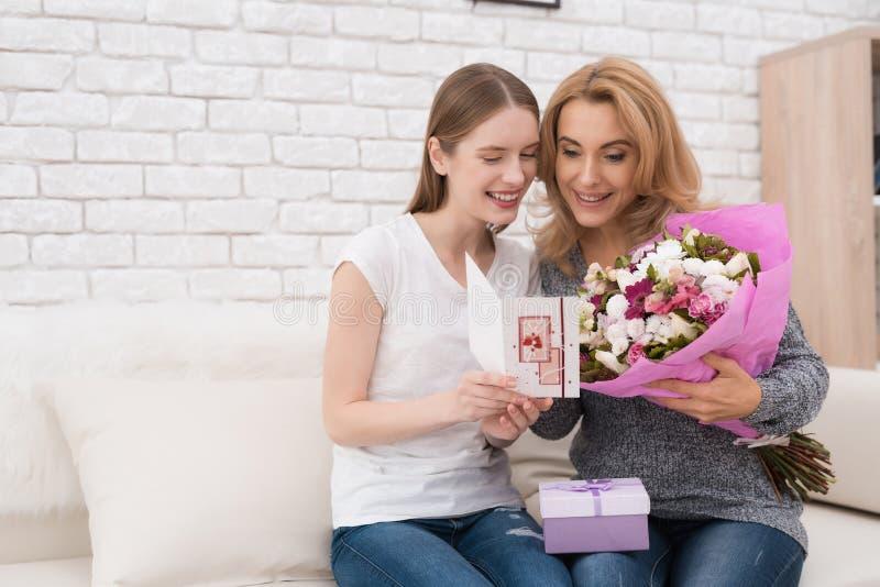 A filha dá-lhe flores e presentes da mãe imagem de stock