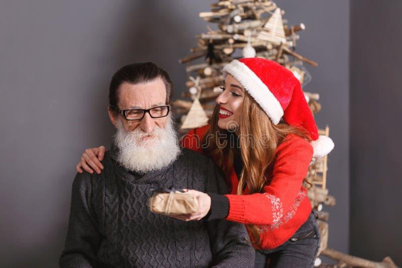 A filha dá um presente a seu paizinho foto de stock