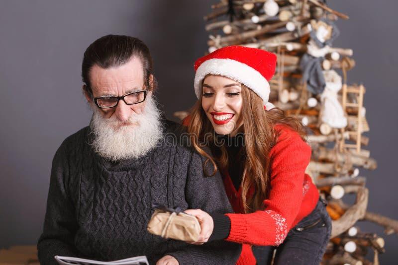 A filha dá um presente a seu paizinho imagem de stock