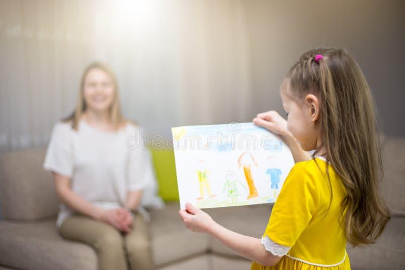 A filha da criança felicita a mamã e dá sua pintura Mum e menina que sorriem e que abraçam Feriado e felicidade da família fotos de stock