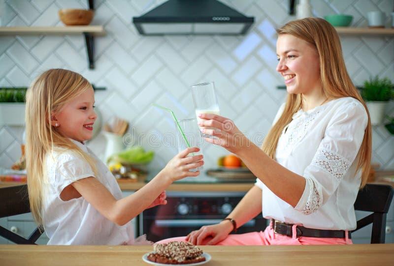 Filha da mãe e da criança na cozinha da casa que come o leite bebendo do divertimento, estilo de vida saudável da família foto de stock royalty free