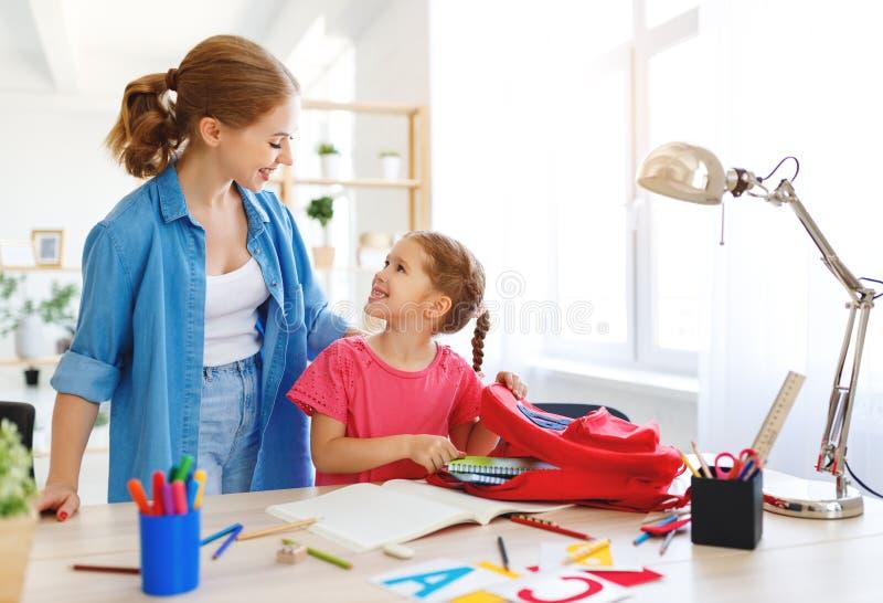 Filha da mãe e da criança que faz a escrita e a leitura dos trabalhos de casa foto de stock royalty free