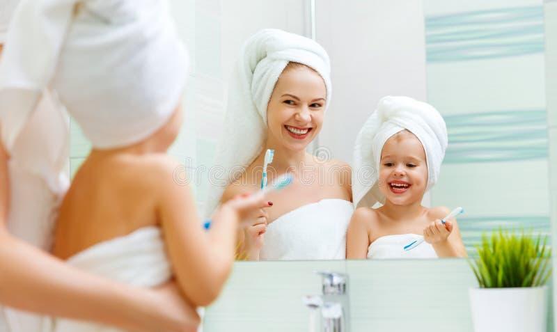 A filha da mãe e da criança escova seus dentes com escova de dentes fotografia de stock royalty free