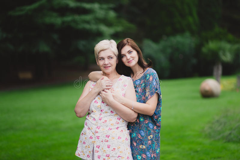 Filha da mãe e do adulto em um parque verde que levanta junto fotos de stock