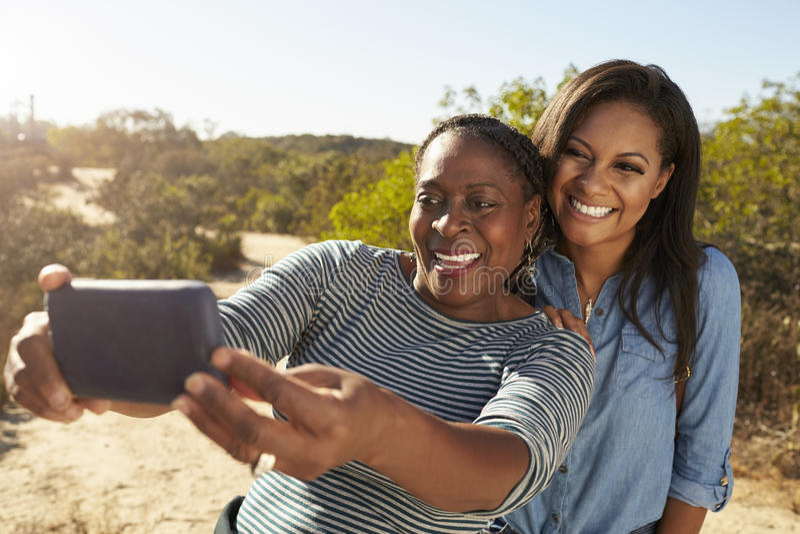 Filha da mãe e do adulto que toma Selfie com o telefone na caminhada foto de stock