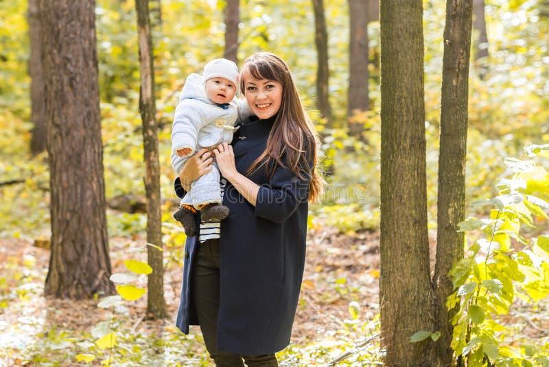 A filha da mãe e do bebê no outono estaciona foto de stock royalty free