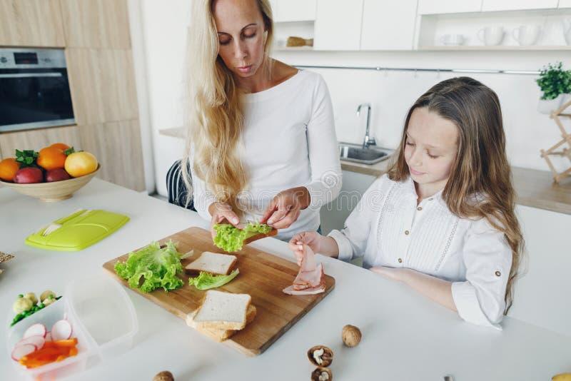 Filha da mãe que prepara a cozinha home do almoço escolar imagens de stock