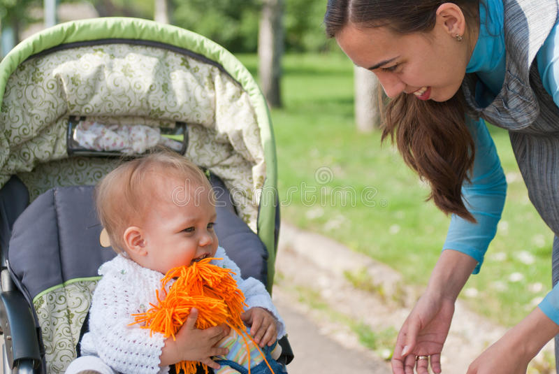 Filha da mamã ao redor em uma cadeira de rodas, parque imagem de stock