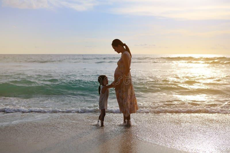 Filha da silhueta que toca na barriga da mãe grávida e que relaxa na praia no por do sol foto de stock royalty free