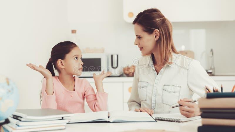 Filha das ajudas da mamã para fazer trabalhos de casa na cozinha foto de stock royalty free