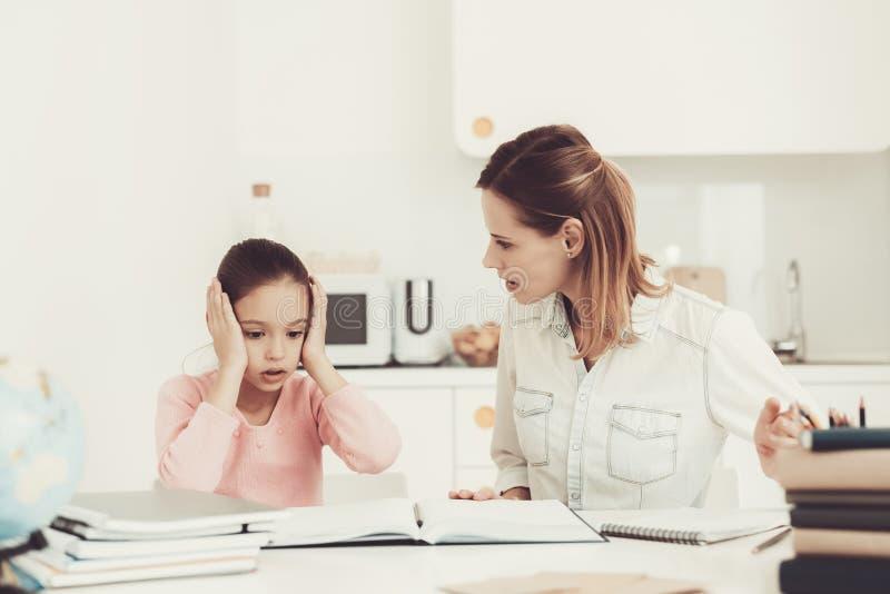 Filha das ajudas da mamã para fazer trabalhos de casa na cozinha fotos de stock