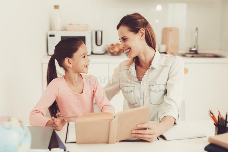 Filha das ajudas da mamã para fazer trabalhos de casa na cozinha fotos de stock royalty free