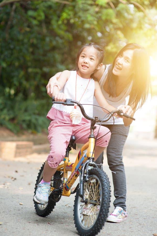 A filha de ajuda da mãe aprende biking exterior foto de stock