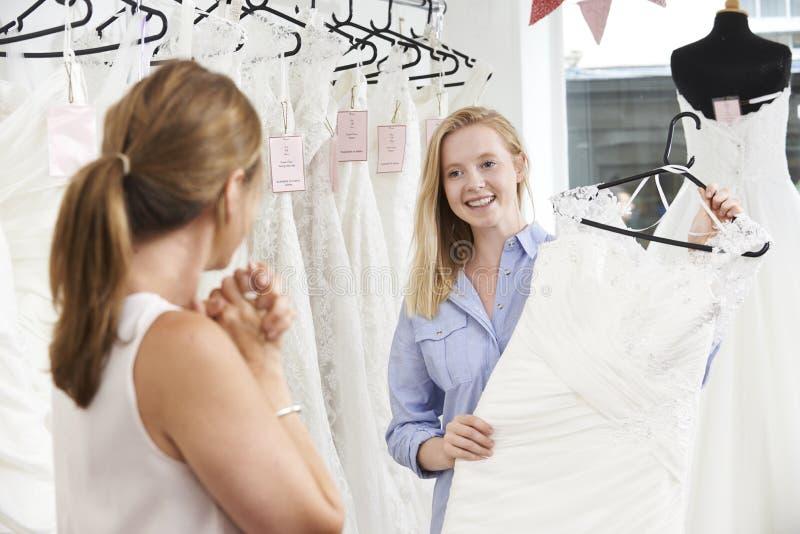Filha de ajuda da mãe para escolher o vestido na loja nupcial imagem de stock royalty free