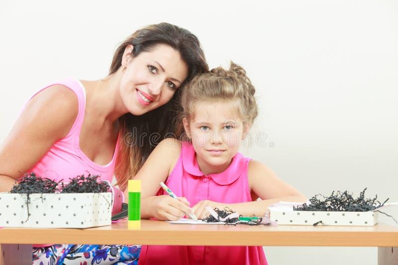 Filha de ajuda da mamã com trabalhos de casa imagem de stock