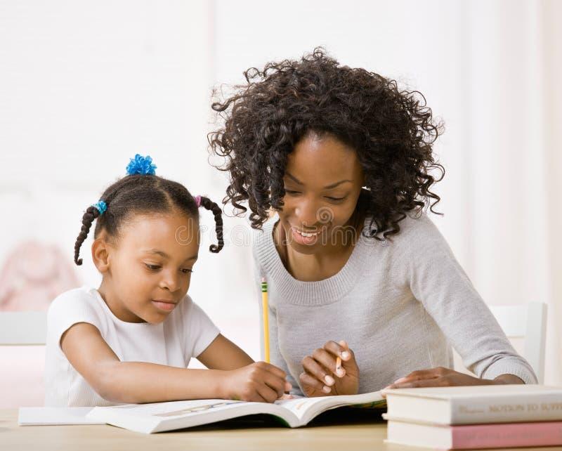 A filha de ajuda da matriz faz trabalhos de casa no manual de instruções