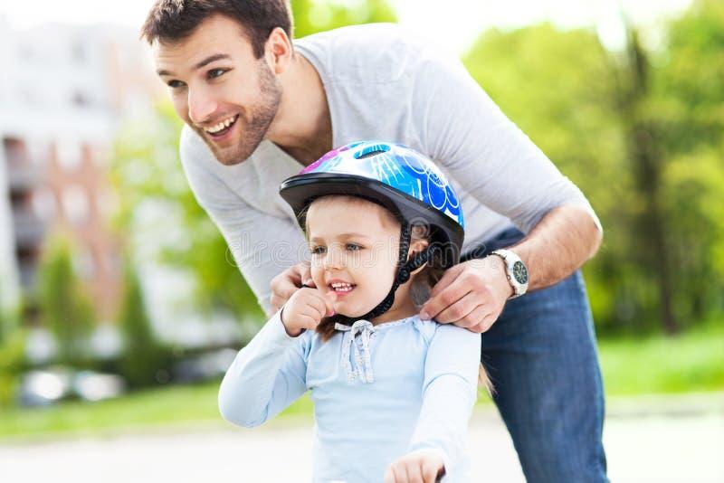 Filha de ajuda do pai com capacete da bicicleta