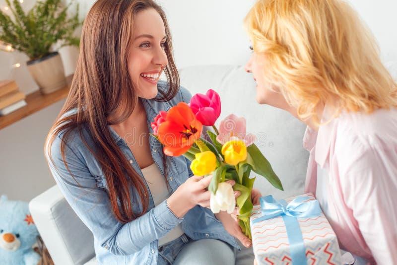 Filha de assento da celebração da mãe e da filha junto em casa que dá flores e presente à mamã foto de stock