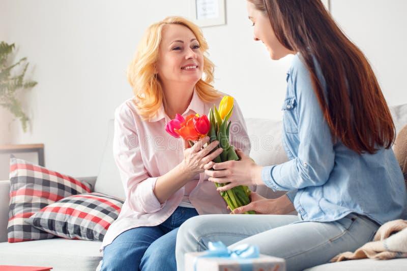 Filha de assento da celebração da mãe e da filha junto em casa que dá a tulipas da mãe o sorriso fotografia de stock