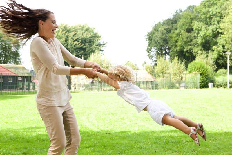 Filha de balanço da mãe nova no parque imagens de stock royalty free