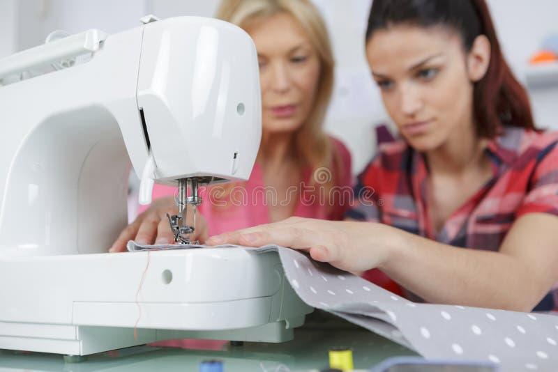 Filha de ensino a costurar fotografia de stock royalty free