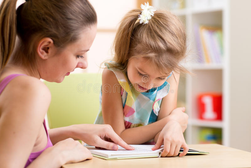 Filha de ensino da criança da mãe a ler imagem de stock royalty free