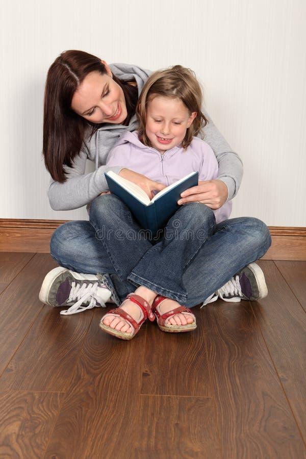 Filha de ensino da matriz para ler a instrução home foto de stock royalty free