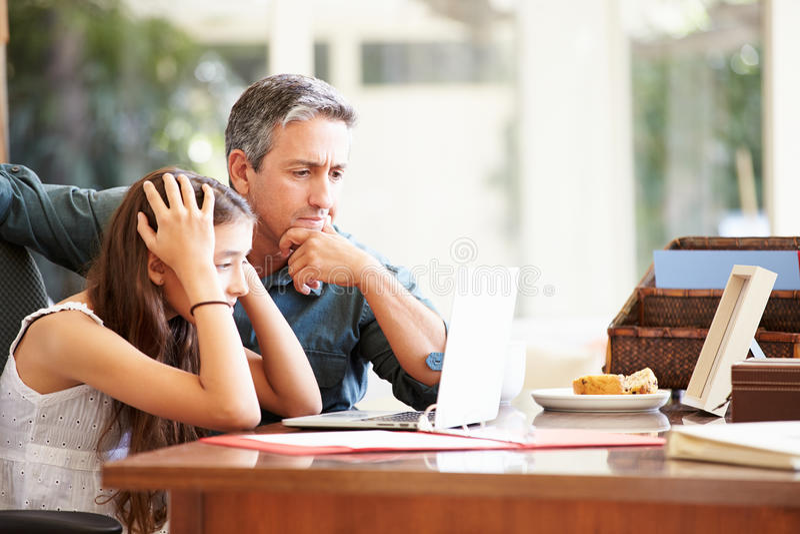 Filha de Helping Stressed Teenage do pai que olha o portátil imagens de stock