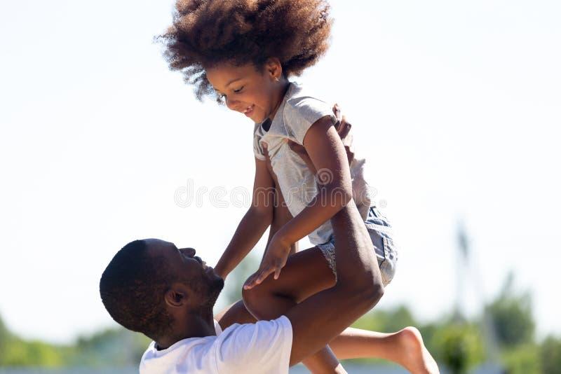 Filha de levantamento do paizinho africano feliz acima de ter o divertimento junto fora fotos de stock