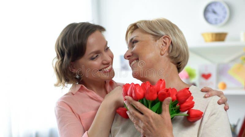 Filha de sorriso que abraça a mãe superior, guardando tulipas presente, cumprimentos do feriado fotografia de stock royalty free