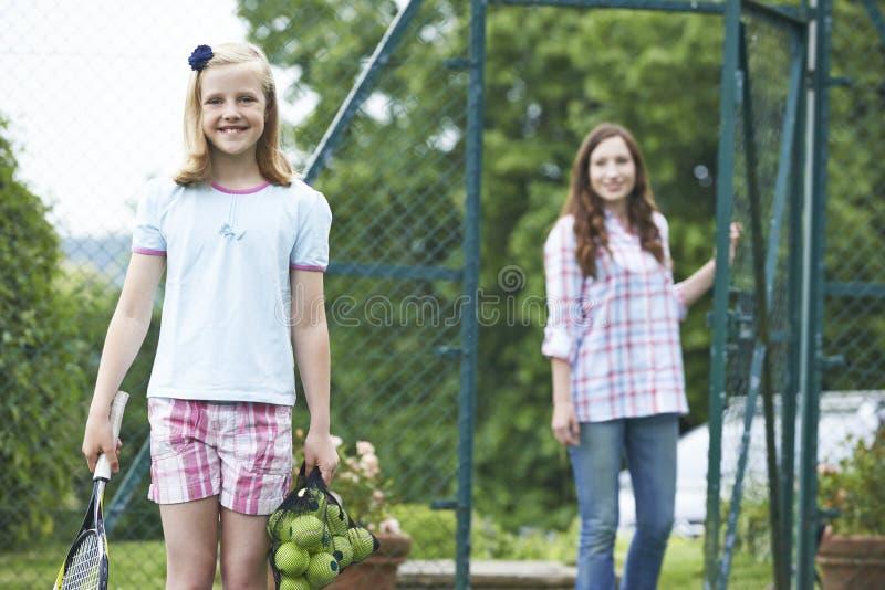 Filha deixando cair da mãe fora para a lição de tênis fotografia de stock
