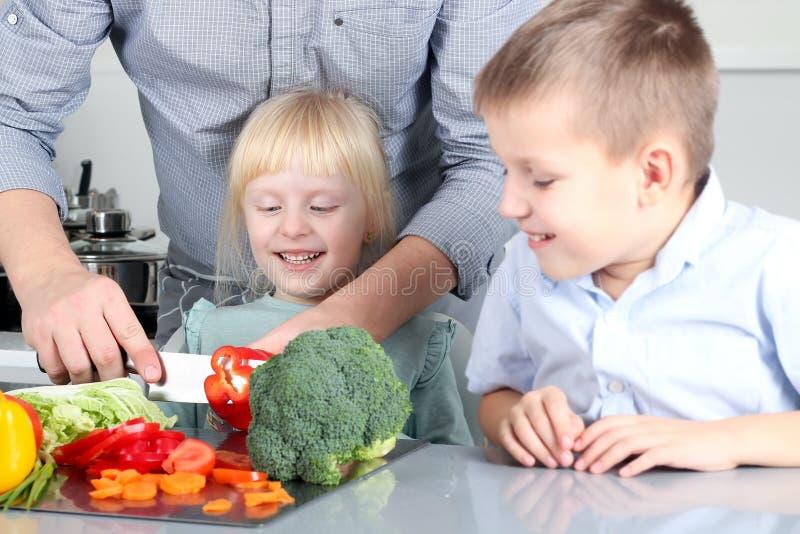 Filha e filho bonitos de sorriso que cozinham um jantar Crianças pequenas que desbastam uma pimenta colorida com pai imagens de stock
