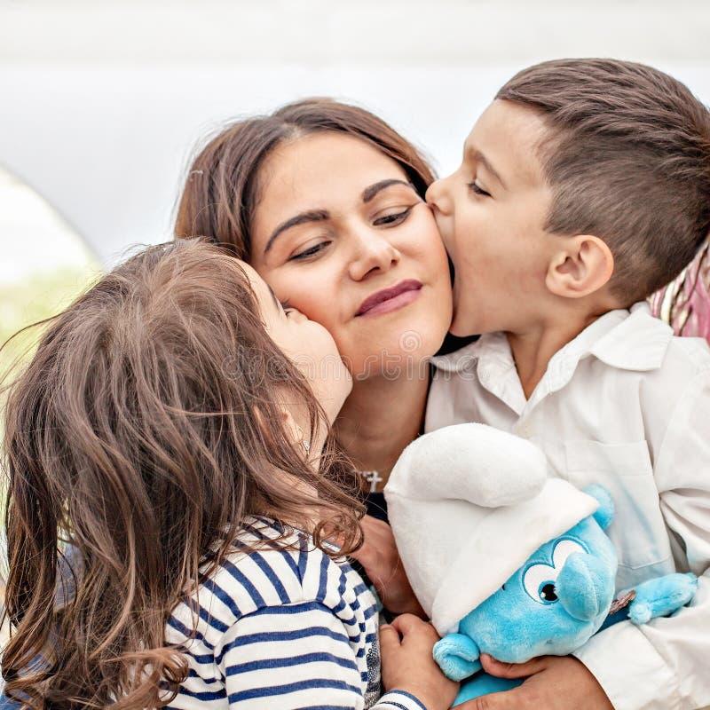 Filha e filho da mãe da foto As crianças beijam sua mãe Foto emocional imagem de stock royalty free