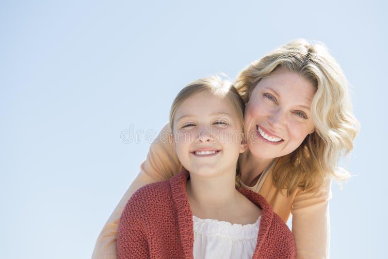 Filha e mãe felizes contra o céu azul claro fotografia de stock
