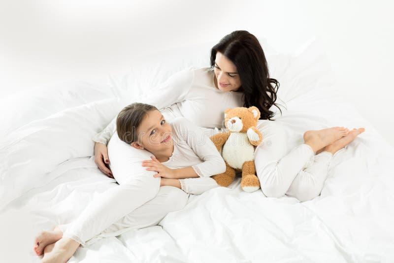 Filha e mãe que encontram-se e que relaxam na cama em casa fotografia de stock