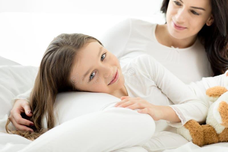 Filha e mãe que encontram-se e que relaxam na cama em casa fotos de stock
