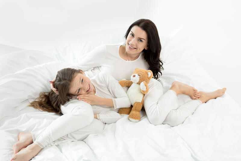 Filha e mãe que encontram-se e que relaxam na cama em casa fotografia de stock royalty free