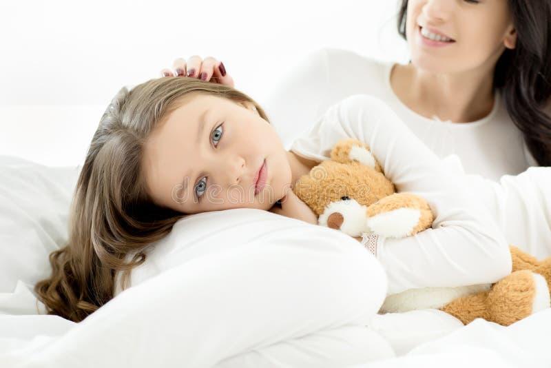 Filha e mãe que encontram-se e que relaxam na cama em casa imagem de stock