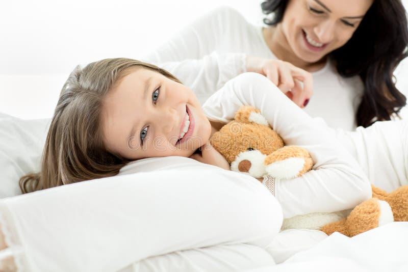 Filha e mãe que encontram-se e que relaxam na cama em casa imagens de stock royalty free