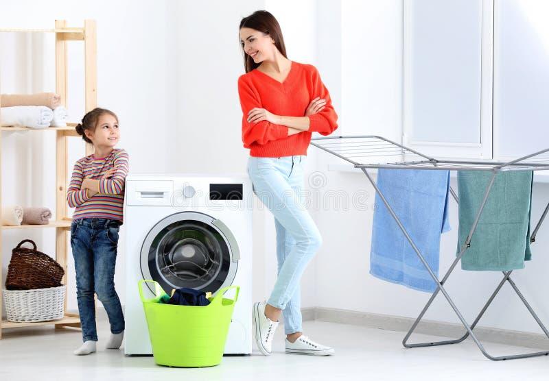 Filha e mãe que fazem a lavanderia junto foto de stock