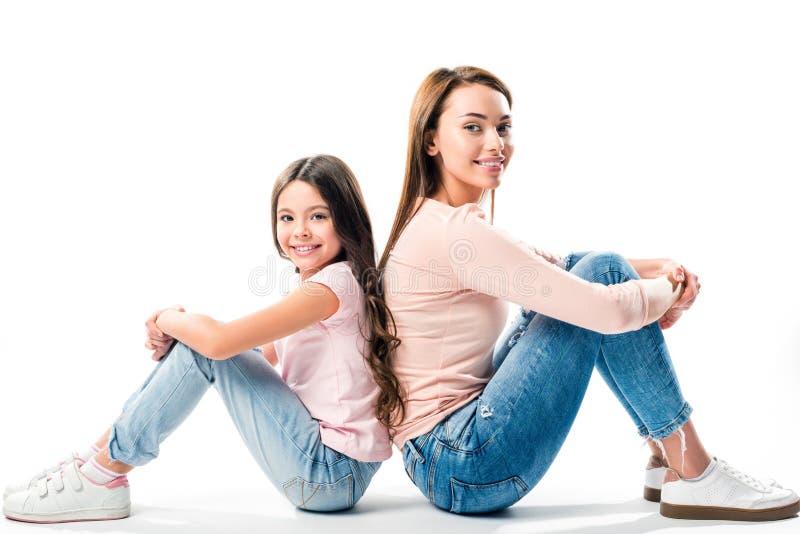 Filha e mãe que sentam-se de volta à parte traseira imagens de stock royalty free