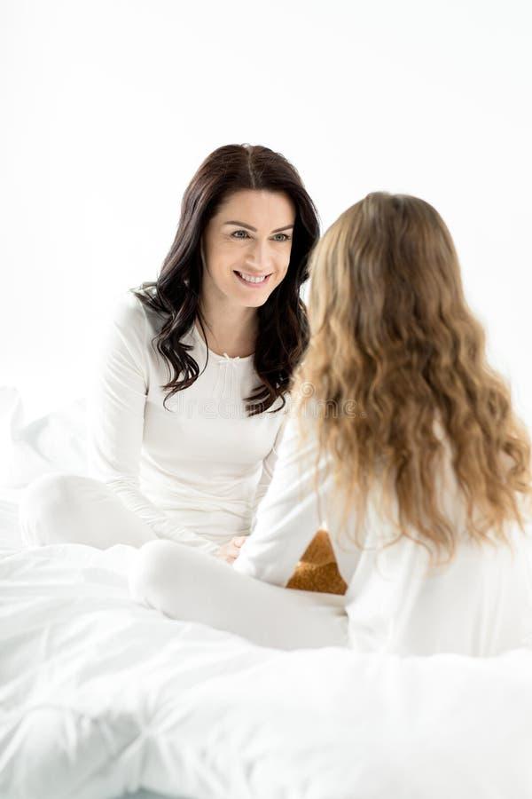 Filha e mãe que sentam-se e que relaxam na cama em casa fotografia de stock royalty free
