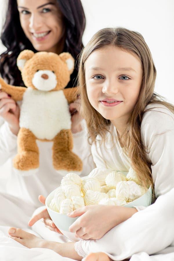 Filha e mãe que sentam-se na cama com marshmallows e urso de peluche foto de stock