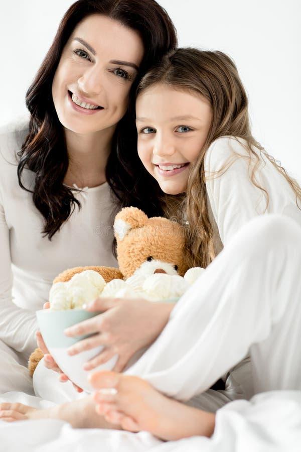 Filha e mãe que sentam-se na cama com marshmallows em casa foto de stock royalty free