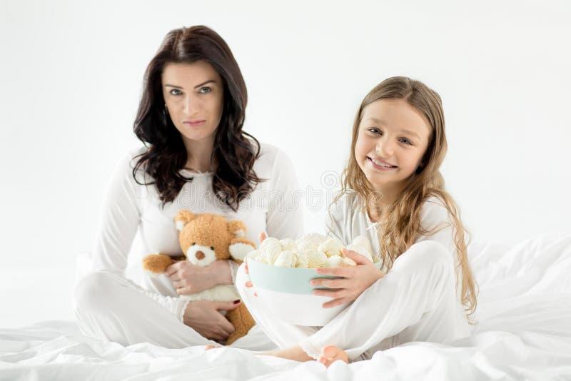 Filha e mãe que sentam-se na cama com marshmallows em casa imagem de stock royalty free